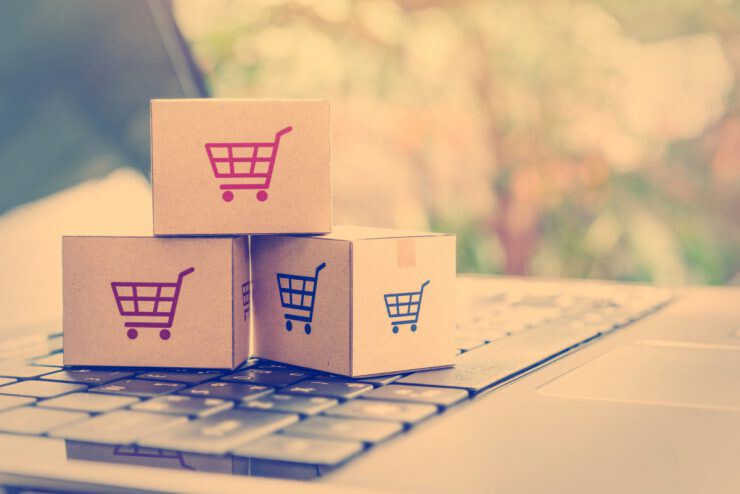 e commerce and delivery service concept : Paper cartons with a shopping cart or trolley logo on a laptop keyboard, depicts customers order things from retailer sites via the internet - nalar.id